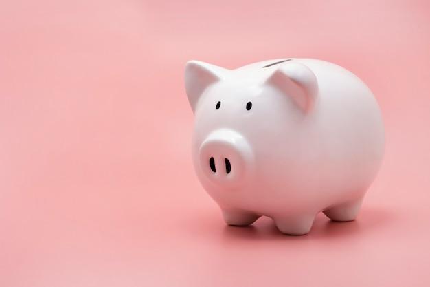 Salvadanaio bianco per risparmiare denaro isolato su sfondo rosa pastello con spazio di copia.