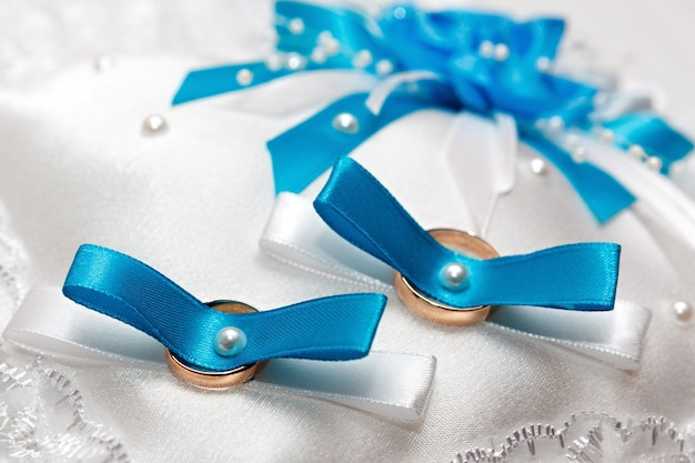 Cuscino bianco per fedi nuziali con nastri blu