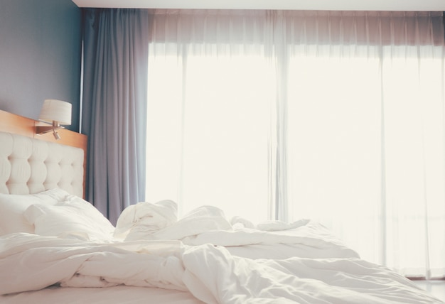 Cuscini bianchi e lenzuola in una camera d'albergo pulita con sfondo vista mattutina