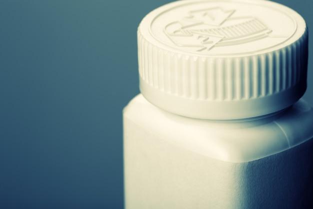 Bottiglia di pillole bianca. tonica in blu