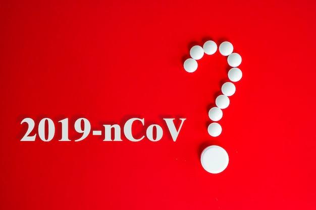 Pillole bianche sotto forma di punto interrogativo su sfondo rosso con iscrizione 2019-ncov e copia spazio per il testo. 2019 nuovo concetto di coronavirus 2019-ncov.