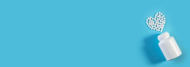 Pillole bianche a forma di cuore con bottiglia su sfondo blu. mock up per pubblicità o altre idee. concetto medico e sanitario. banner largo medico con spazio per il testo.