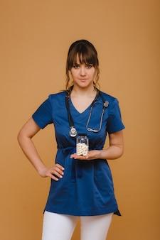 Pillole bianche in un barattolo di una dottoressa. il medico mostra le capsule vitaminiche capsule medicinali.