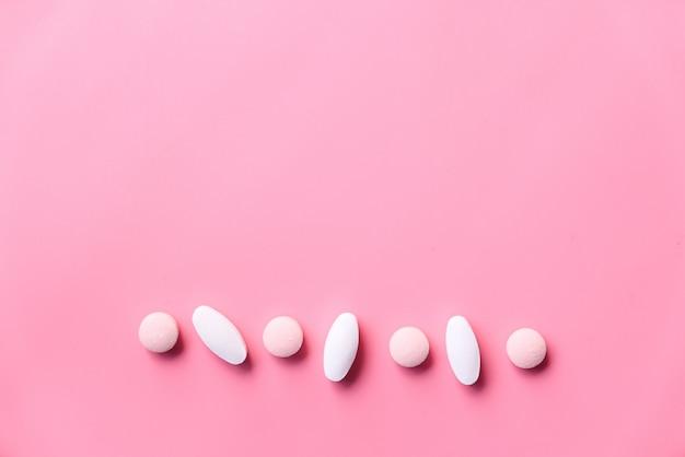 Pillole bianche che si rovesciano nello spazio rosa con lo spazio della copia