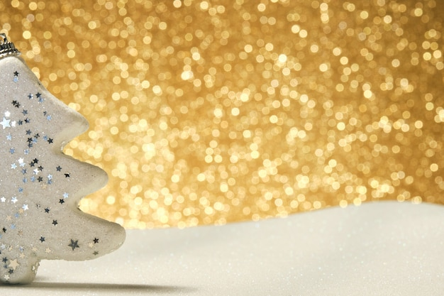 Ornamento natalizio a forma di pino bianco sul lato sinistro dell'immagine su una superficie che imita la neve con uno sfondo dorato lucido sfocato