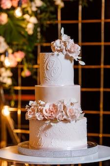 Bella torta nuziale bianco-rosa sullo sfondo dell'arco nuziale serale.
