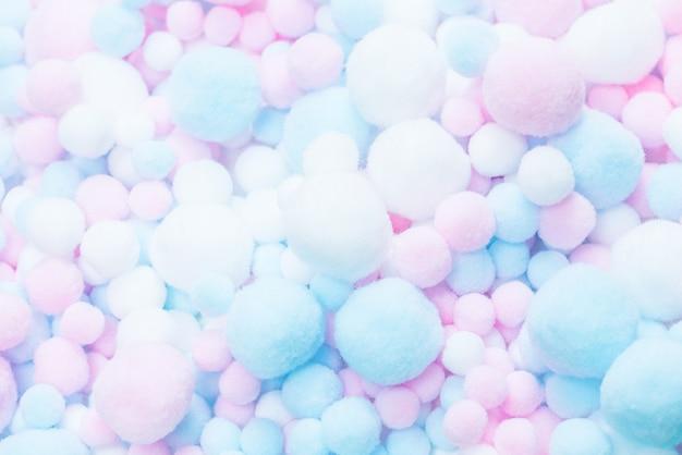 Sfondo di pompon morbidi bianchi, rosa e blu.