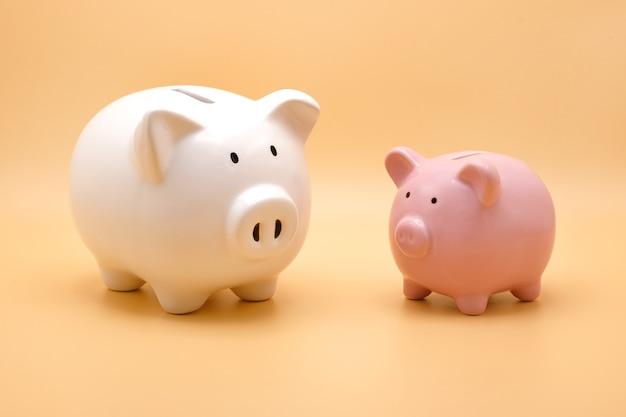 Salvadanaio bianco e rosa per risparmiare denaro isolato su sfondo arancione pastello