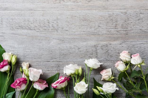 Rose bianche e rosa su fondo in legno chiaro con spazio di copia.