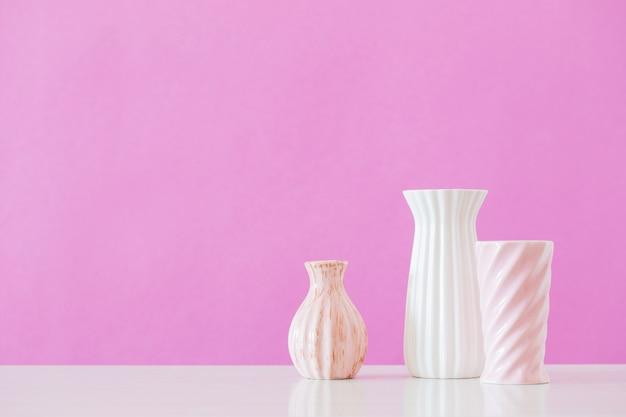 Vasi bianchi e rosa su sfondo rosa