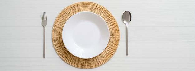 Tavolo da pranzo bianco della plancia con il piatto ceramico bianco su tovaglietta e argenteria