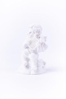 La figura in gesso bianco di un angelo suona musica in stile classico su bianco