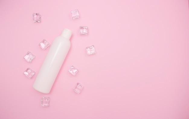 Bottiglia di plastica bianca per shampoo o altri cosmetici su uno sfondo rosa tra i cubetti di ghiaccio