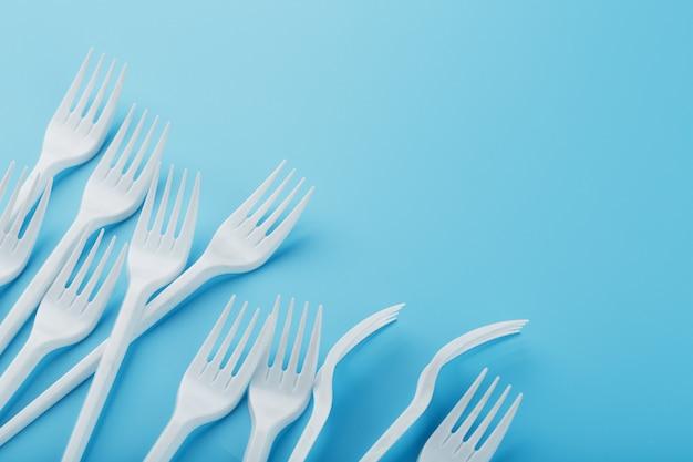 Forchette di plastica bianche di articoli per la tavola a gettare sul blu.