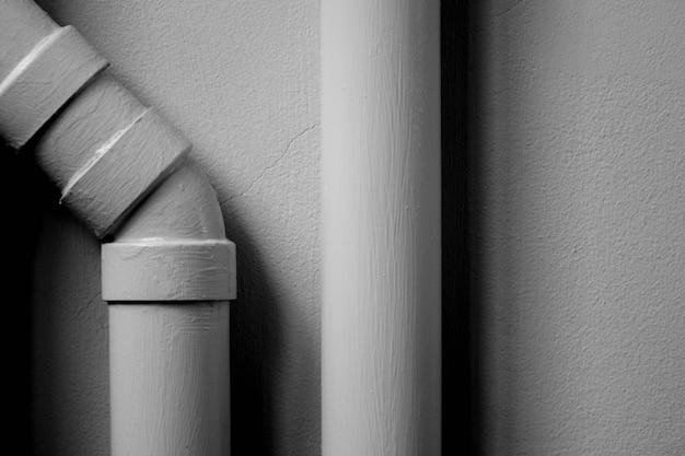 Tubo di plastica bianco al muro di cemento bianco con ombra.