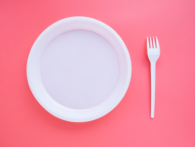 Piatto di plastica bianco e forchetta su sfondo rosa