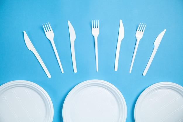 Piatti di plastica bianchi, forchette e coltelli su sfondo blu.