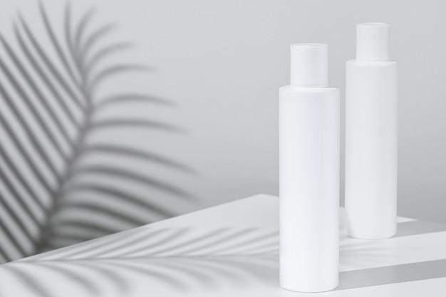 Tubi per la cura della pelle di plastica bianchi con l'ombra della pianta tropicale
