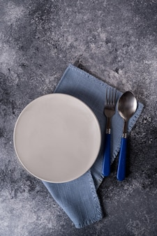 Piatto bianco sul tovagliolo blu sulla tavola di legno grigia
