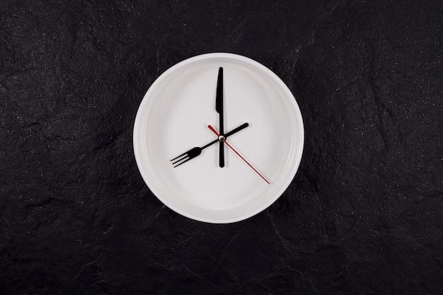 Orologio piatto bianco su una pietra strutturata scura