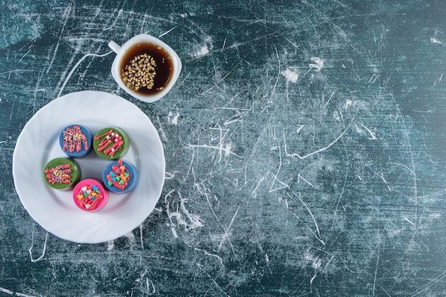 Un piatto bianco di cupcakes colorati con spruzza e una tazza di tè nero.