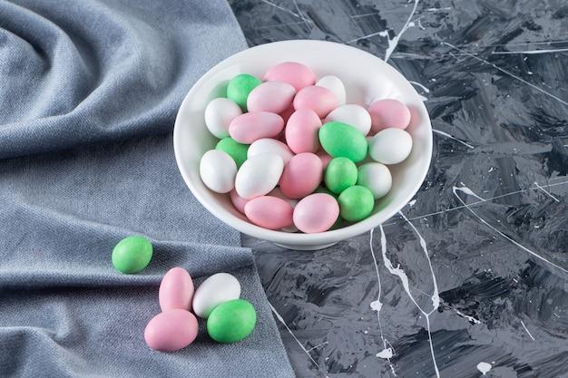 Piatto bianco pieno di caramelle colorate sul tavolo di marmo.