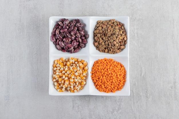 Piatto bianco pieno di lenticchie crude, semi e fagioli su fondo di pietra.
