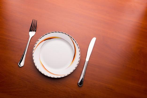 Piatto bianco, coltello e forchetta sul tavolo di legno
