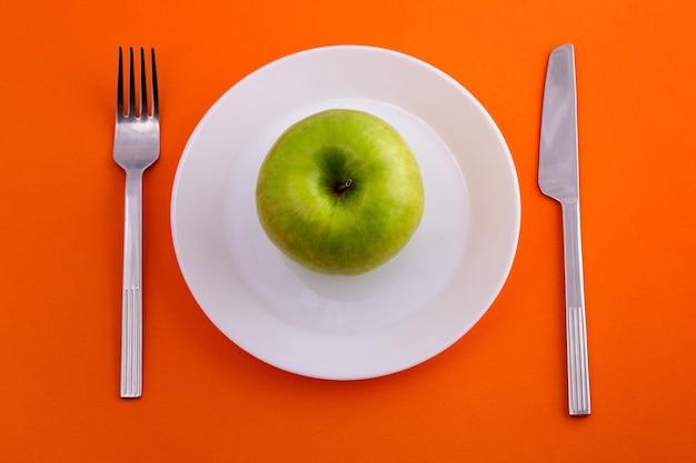 Su un piatto bianco giace una mela verde un coltello con una forchetta su uno sfondo arancione vista dall'alto...