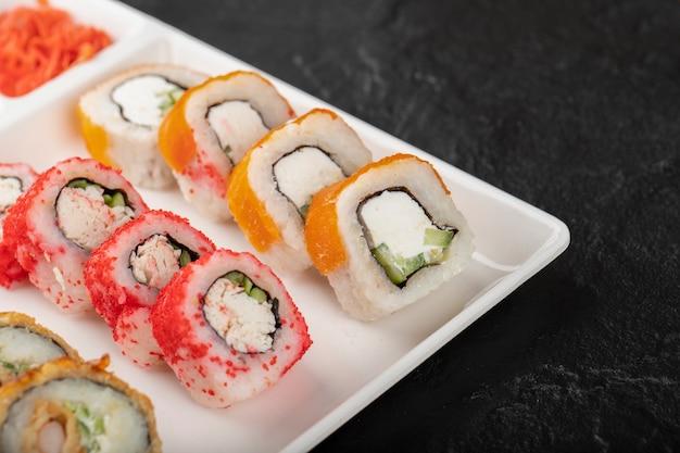 Piatto bianco di vari rotoli di sushi su sfondo nero.
