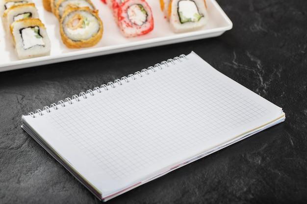 Piatto bianco di vari rotoli di sushi e notebook su sfondo nero.