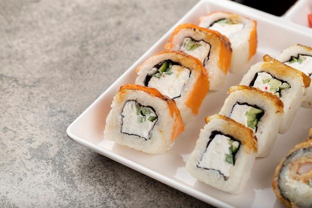 Piatto bianco di vari rotoli di sushi su sfondo di pietra.