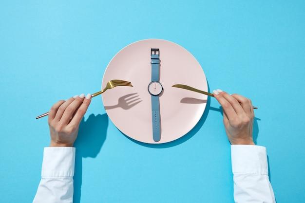 Il piatto bianco con fascia blu mostra il coltello e la forchetta serviti alle sei in mano a una ragazza su una parete blu, posto per il testo. tempo per mangiare e concetto di dieta. vista dall'alto.