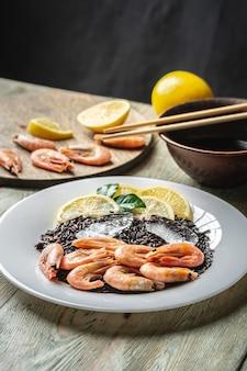 Un piatto bianco con un appetitoso piatto congelato di gamberetti e riso nero con limone su un tavolo di legno