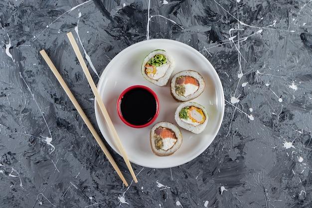 Piatto bianco con rotolo di sushi di cetriolo su superficie di marmo.