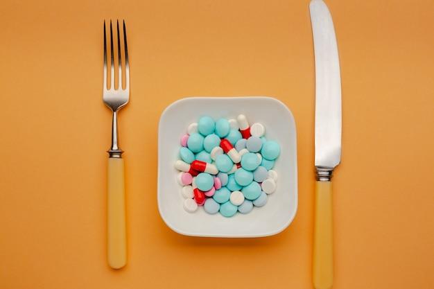 Piatto bianco con diverse pillole su di esso con coltello e forchetta concetto di tossicodipendenza