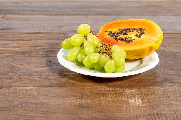 Piatto bianco con frutta: papaia e uva, su un tavolo in legno rustico