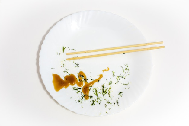 Piatto bianco con cibo avanzato e bacchette di sushi, cibo mangiato, vista dall'alto