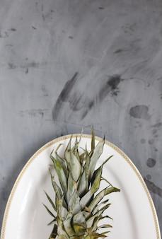 Piastra bianca con ananas a fette mature su sfondo grigio cemento. copyspace.