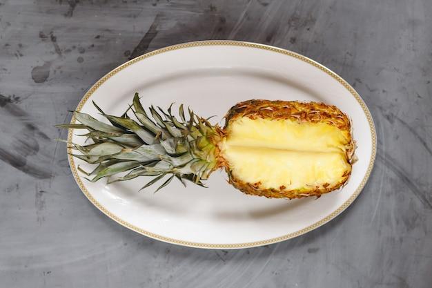 Piastra bianca con ananas a fette mature su sfondo grigio cemento.