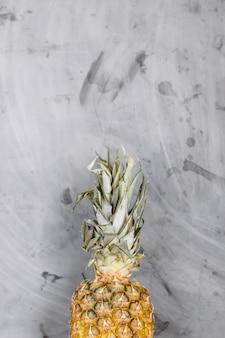 Piatto bianco con ananas intero maturo su sfondo grigio cemento. copyspace.