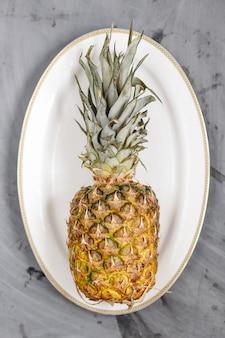 Piatto bianco con ananas intero maturo su sfondo grigio cemento.