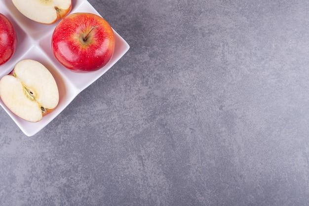 Piatto bianco con mele rosse lucide su fondo di pietra.