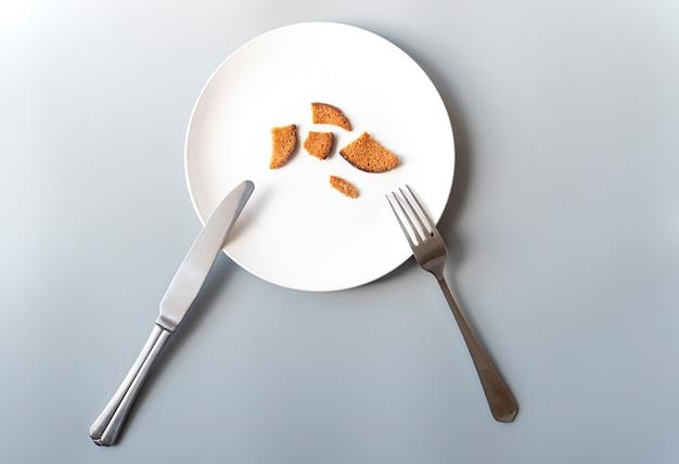 Piatto bianco con alcuni cracker, coltello e forchetta, povertà, fallimento, fame, foto di concetto