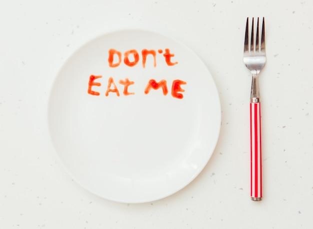 Piatto bianco con il testo non mangiarmi e copia lo spazio