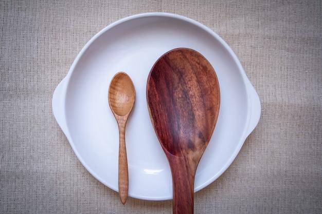 Zolla bianca con un cucchiaio di legno su una tovaglia marrone