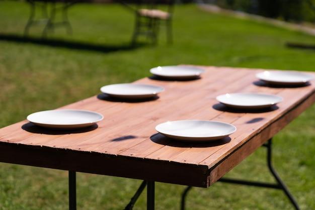 I piatti bianchi sono posizionati su un tavolo di legno nel parco su un prato verde.