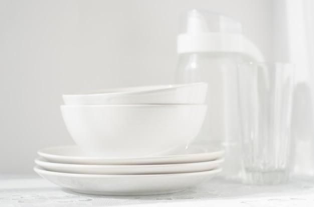 Piatti e ciotole bianche sul tavolo luminoso