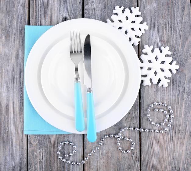 Piatti bianchi, forchetta, coltello e decorazione dell'albero di natale su fondo di legno