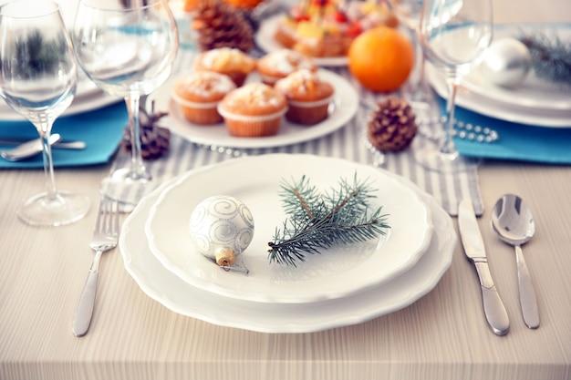 Piatti bianchi con posate su una tavola di natale